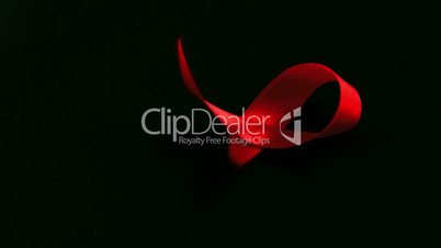 Red ribbon dropping down on black background