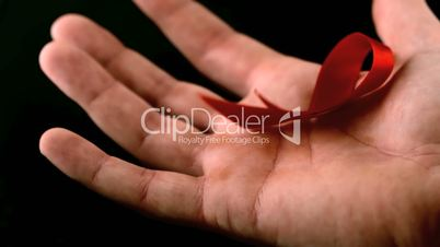 Aids red ribbon symbol falling over a man hand