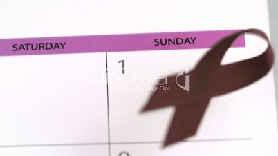 Red ribbon symbol for Aids falling on a calendar