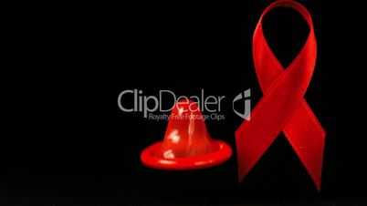 Condom falling over in front of a red ribbon on black background