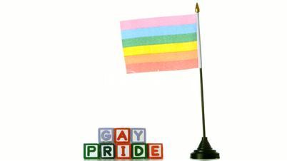 Rainbow flag blowing in the wind beside gay pride blocks on white background