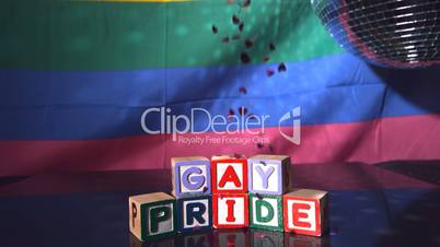 Heart confetti falling on blocks spelling gay pride