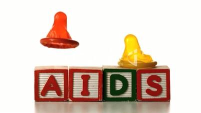 Condom falling on blocks spelling AIDS