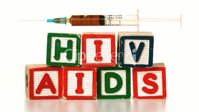 Needle falling on blocks spelling AIDS and HIV