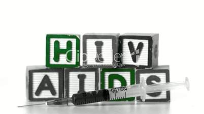 Needle falling in front of blocks spelling AIDS and HIV