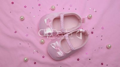 Pink baby booties on pink blanket with pearls