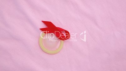 Condom and red ribbon