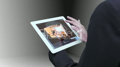 Businesswoman using tablet to view montage of lifestyle clips