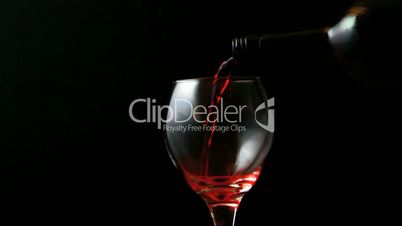 Glass of red wine being poured