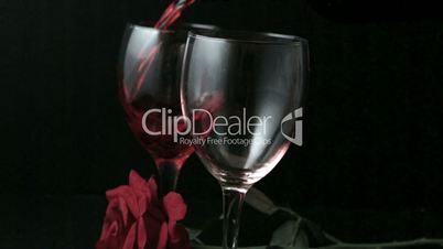 Two glasses of red wine being poured with red rose