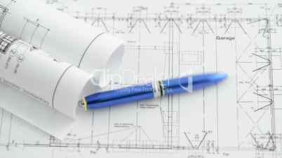 A pen rolls over  an architectural drawing blueprint.
