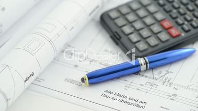 blueprint with calculator and pen