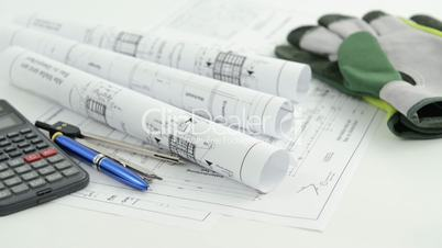 blueprint with calculator pen and work gloves