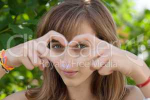 Teenage girl forming heart with her hands