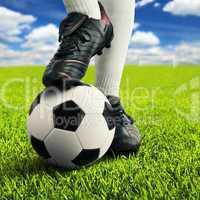Ball und Füße eines Fußballers in lässiger Pose