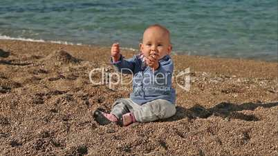 Baby sitting on beach playing with little stones