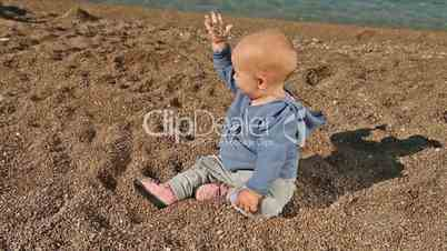 Baby on beach playing and talking