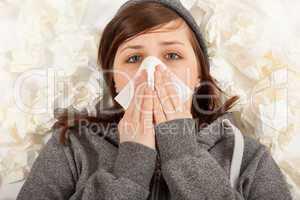 Das junge Mädchen liegt krank im Bett und putzt sich die Nase