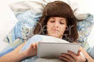Das junge Mädchen liegt krank im Bett und schaut in ihr Tablett