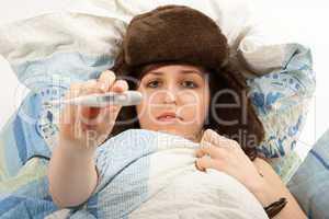 Das junge Mädchen liegt krank im Bett und misst Fieber