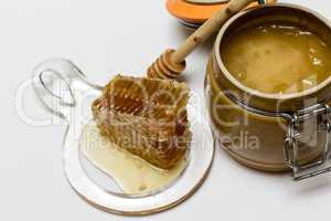 Honey in pot, honeycomb and stick