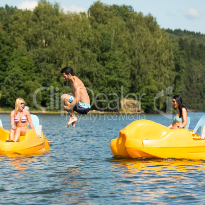 Young man jumping into water paddle boat