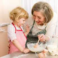 Child girl and grandmother baking cake