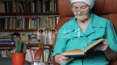 old woman sitting on chair and reading book