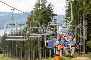Waving young people sitting on chairlift