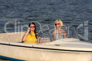 Young women in sunglasses sitting in motorboat