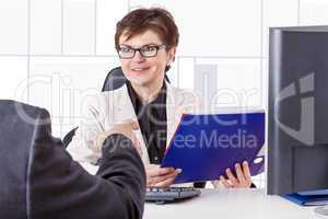 Business woman with folder speaks to man in a suit