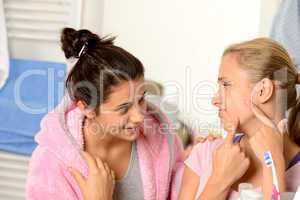 Teenage girls having acne problems in bathroom