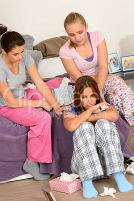 Teenager girls comfort crying friend in bedroom