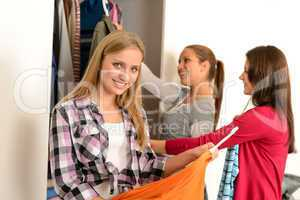 Happy teenagers choosing clothes from wardrobe