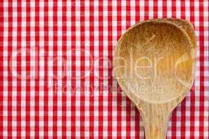 Antiker Kochlöffel aus Holz mit Hintergrund rot weiß