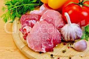 Meat slices on a wooden board with vegetables