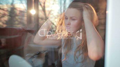 Through the window warm portrait of girl enjoying her hair. Beautiful back light.