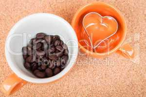 Cup of coffee bean and cookies cutter on cork background