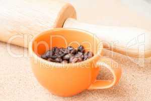 Cup of roast coffee bean and roller on cork background