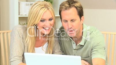 Happy Young Couple Having Online Success on Laptop