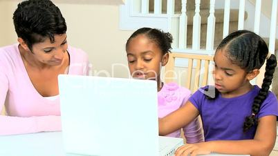 Ethnic Mother Watching Daughters Using Laptop
