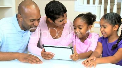 Young Parents Watching Children Using Wireless Tablet