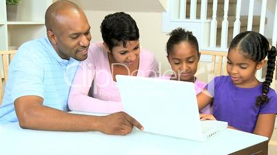 Ethnic Parents Watching Daughters Using Laptop
