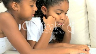 Little Ethnic Girls at Home Using Laptop