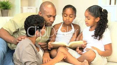 Young Ethnic Child Reading Aloud to Family