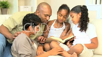 Little Ethnic Girl Reading a Book to her Family