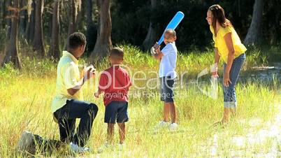 Active Ethnic Family Playing Baseball in Park