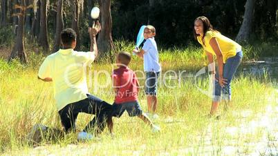 Young African American Family Playing Baseball in Park