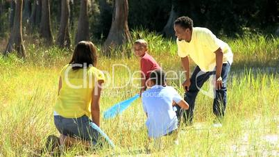 African American Family Playing Baseball in Park