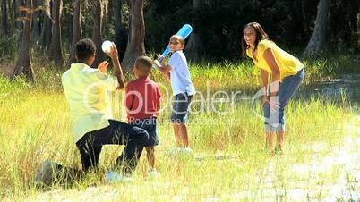 Ethnic Family Playing Baseball in Park